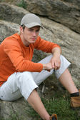 Young man sitting on some rocks — Stock Photo