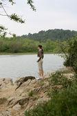 Woman on a riverbank — Stock Photo
