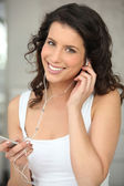 Young woman listing to an MP3 player — Stock Photo