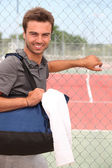 Smiling male tennis player with kitbag outside court — Stock Photo