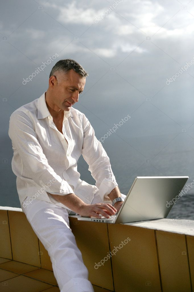 Man working on his laptop by the ocean — Stock Photo #8555523
