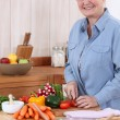 Stock Photo: Old lady chopping vegetables