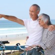 Senior couple having bike ride at the beach — Stock Photo