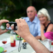 Stock Photo: Senior taking photograph of couple