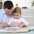 Young girl colouring with her father — Stock Photo #8561495