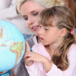 Mum and daughter looking at a globe — Stock Photo #8561534