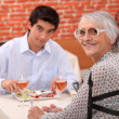 Young man and elderly woman in a restaurant — Stock Photo