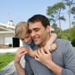 Stock Photo: Father giving kid piggy-back in garden