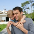 Father giving kid piggy-back in the garden — Stock Photo #8561850