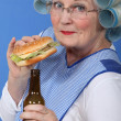 Old woman in rollers with a burger and a beer — Stock Photo