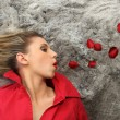 Blonde in red blowing away red rose petals — Stock Photo #8565713