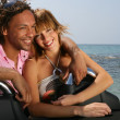 Young couple at the beach stood by convertible car — Stock Photo