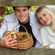 Young couple behind a wooden barrier in autumn, the man is holding a wicker — Stock Photo