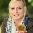 Woman holding a spiky chestnut case - Lizenzfreies Foto