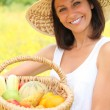 Stock Photo: Woman carrying fruits in basket