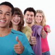 Group of young giving the thumbs-up — Stock Photo