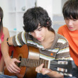 Stock Photo: Teens listening to their peer play guitar