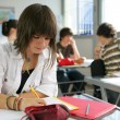 A teenage girl studying in a classroom - Foto Stock