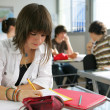 A teenage girl studying in a classroom — Stock Photo