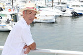 Older man in a straw panama hat standing by a marina — Stock Photo