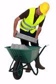 Craftsman putting stones in a wheelbarrow — Stock Photo