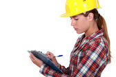 Tradeswoman filling in paperwork — Stock Photo