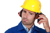 Man wearing safety earmuffs and helmet — Stock Photo
