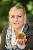 Woman holding a spiky chestnut case — Stock Photo