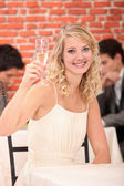 Blonde woman with a glass of white wine — Stock Photo