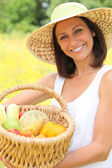 Woman carrying fruits in basket — Stock Photo