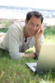 Man smiling working on the grass — Stock Photo
