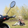 Stock Photo: Couple sat near scooter
