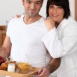 A man bringing breakfast on a platter and his wife wearing a bathrobe — Stock Photo #8571181