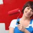 Woman painting wall red with roller — Stock Photo #8571285