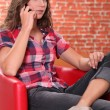 Woman sat on leather chair speaking on mobile telephone — Stock Photo #8571963