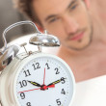 Ringing alarm clock waking up a man — Stock Photo