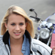 Teenage girl with motorbike and driving licence — Stock Photo