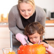 Mother and daughter carving jack-o-lanterns — Stock Photo #8575656