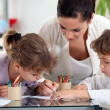 Young woman and little girls making coloring — Stockfoto