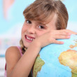 Young girl hugging a globe - Stockfoto