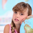A little girl learning geography. — Stock Photo