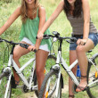 Two teenage girls riding bikes in countryside - Stock Photo