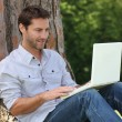 Man sat by tree with laptop — Stock Photo
