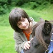 Boy caressing a pony — Stockfoto