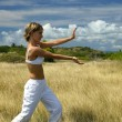 Woman doing exercises in a field - Stock Photo