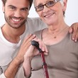 Smiling young man with his arms around a senior woman in glasses — Stock Photo