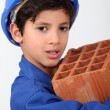 Stock Photo: Little boy carrying brick