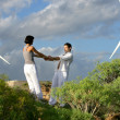 Foto Stock: Couple stood by wind farm