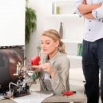 A female technician repairing a television — Stock Photo #8579355