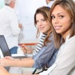 Young women smiling in classroom — Stock Photo #8579666